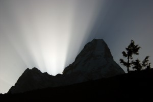 At dawn, sun beams spread star-like into space behind the sacred peak of Ama Dablam (6,856 m), Khumbu, E Nepal Ved daggry spredes den opgående sols stråler i stjerneform bag det hellige bjerg Ama Dablam (6856 m), Khumbu, østlige Nepal